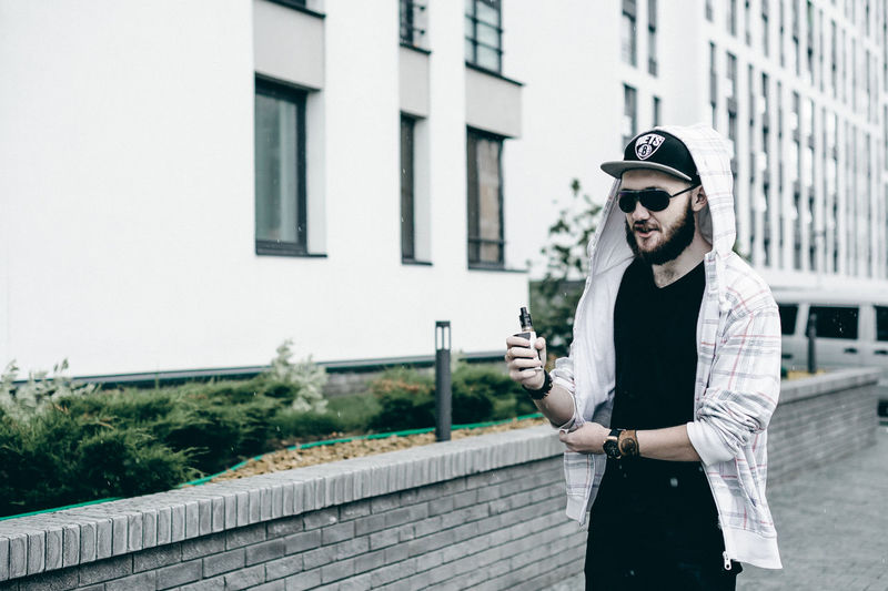 Vaping Architecture Bad Habit Building Exterior Built Structure Cap Casual Clothing City Day Fashion Front View Handsome Leisure Activity Lifestyles Men Mid Adult Men One Person Outdoors Portrait Real People Smiling Standing Sunglasses Young Adult Young Men