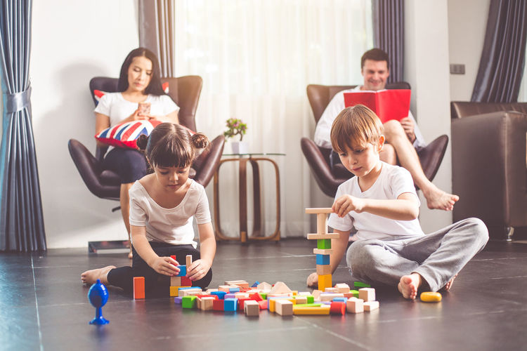 Happy friends sitting on toy at home