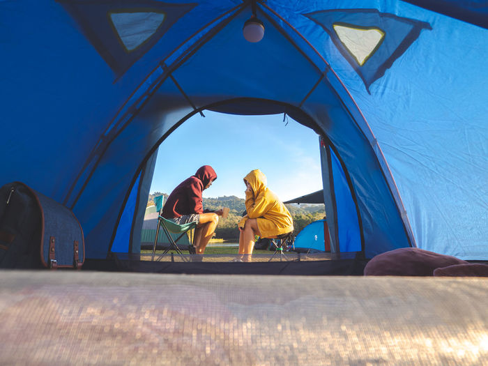 Asian couple sit front of tent camping around mountain lake