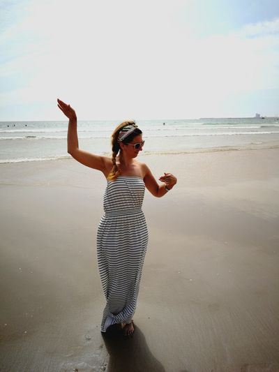 Smiling woman gesturing at beach against sky