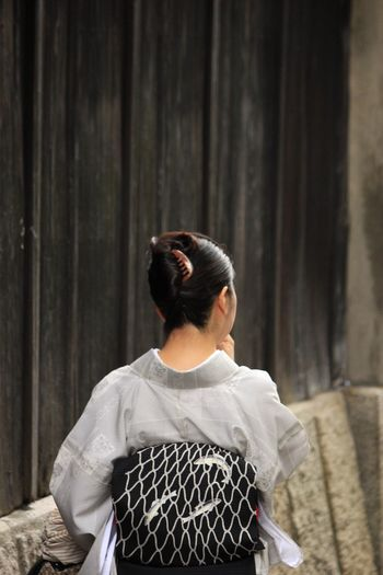 Rear View Of Woman In Kimono Standing By Wall