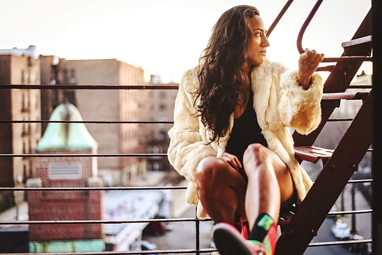 Young woman sitting on railing