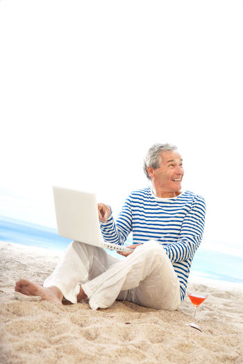 Rear view of senior man using phone while sitting on beach