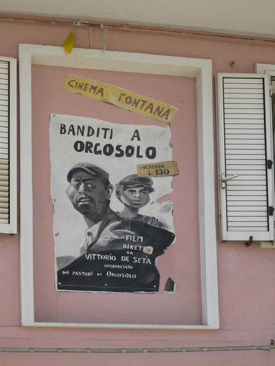 Wall with Cinema handpainted poster Orgosolo touristic destinations sadegna, sardinia, Sardinien, Sardenia Advertising Gangster Film Cinema Poster Cinema Film Filmplakat Graffiti Orgosolo Walll Text Communication Message Outdoors Close-up