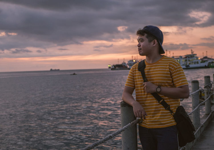 Young man looking at sea against sky