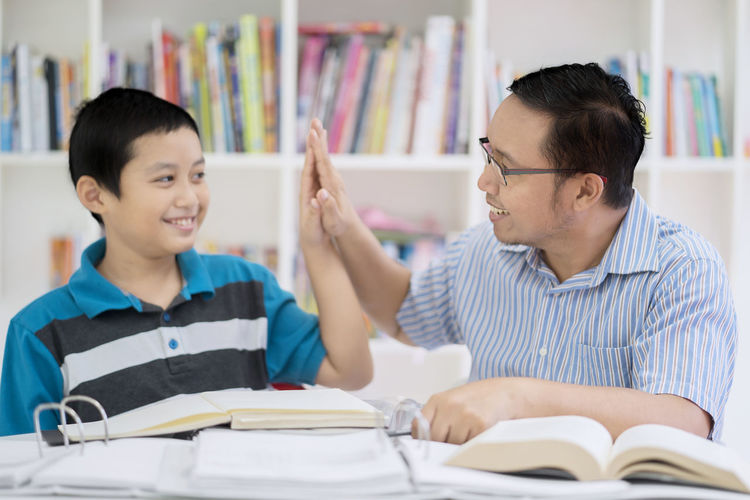 Boy with teacher at table in school