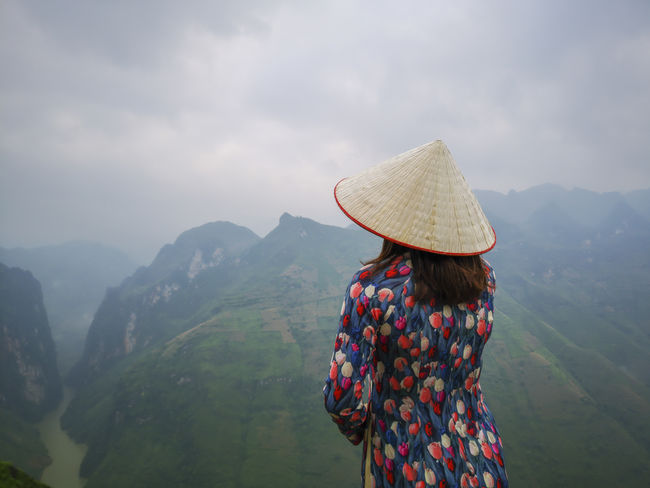Young Vietnamese women facing and pose for camera with stunning view of the Nho Que river surrounded by mountains from the Ma Pi Leng pass in northern Vietnam Mountain Cloudy Green Color Meo Vac Vietnam Vietnamese Adult Ao Dai Beauty In Nature Casual Clothing Clothing Cloud - Sky Day Hat Landscape Leisure Activity Lifestyles Looking At View Mountain Mountain Range Nature One Person Outdoors People Pose Real People Rear View Scenics - Nature Sky Standing Sunrise Traditional Dress Valley Women