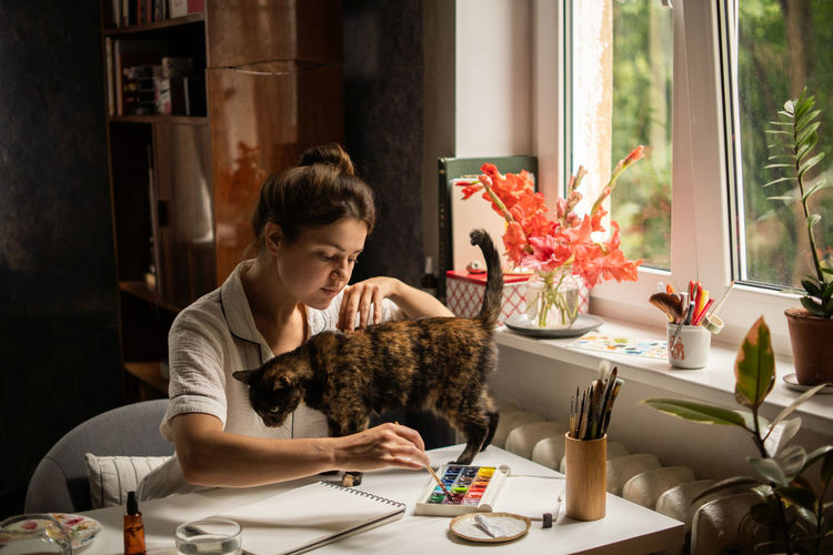 Female painter artist making an abstract watercolor painting. painting with cat
