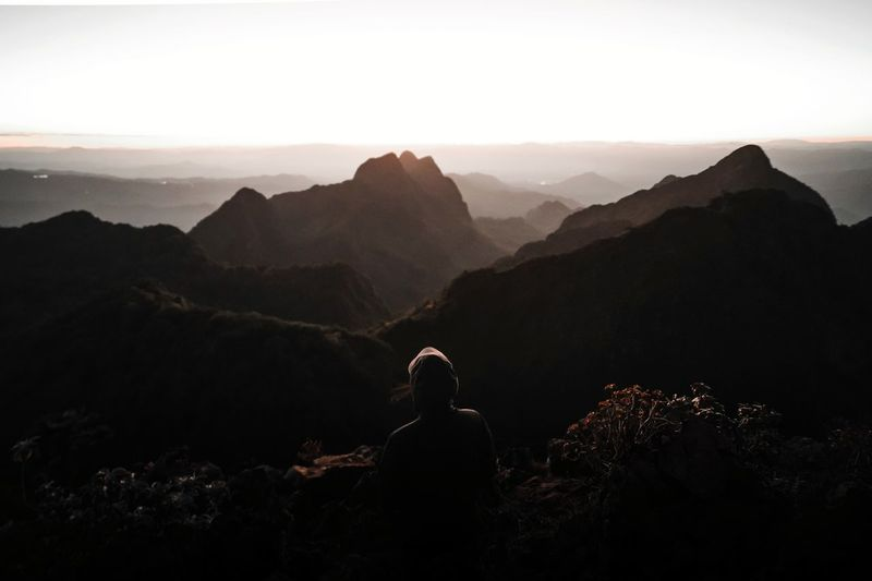 Rear view of sad man looking sunset at mountain range against sky