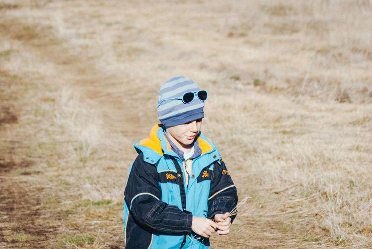 Boy standing on grassy field