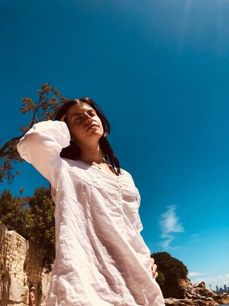 Savour the sun Model Summer People Love Beach Sun Photography EyeEmNewHere EyeEm Selects Low Angle View Blue Day Sky Outdoors One Person Standing Real People Young Women Young Adult Clear Sky Nature Statue Women Beauty In Nature Tree