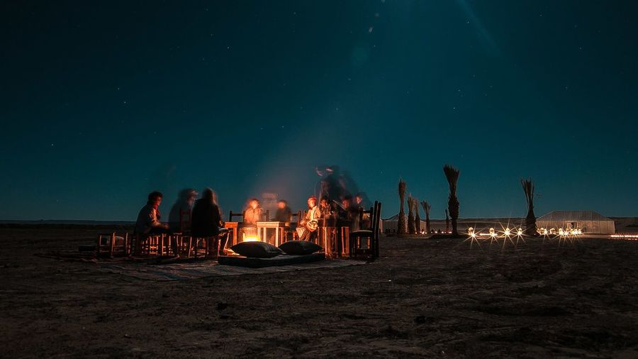 People by bonfire at beach against sky during night