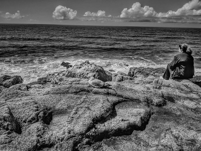 Woman sitting alone contemplating the vastness of the sea. monochrome.
