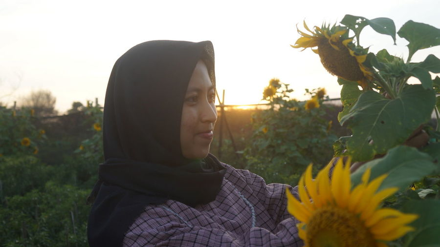 Woman Standing By Sunflower Against Sky