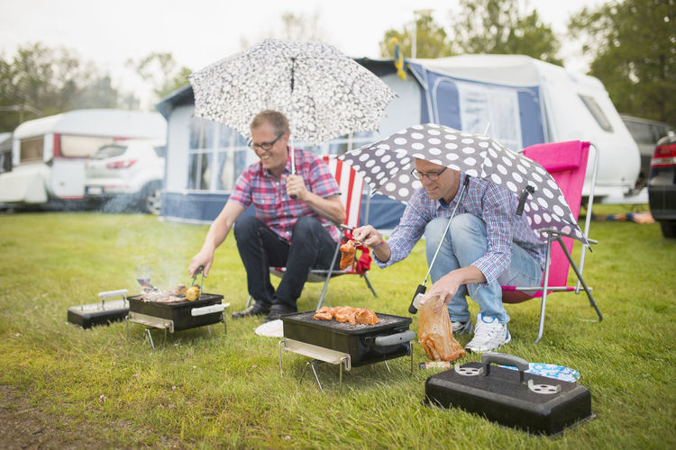 Friends standing on barbecue grill