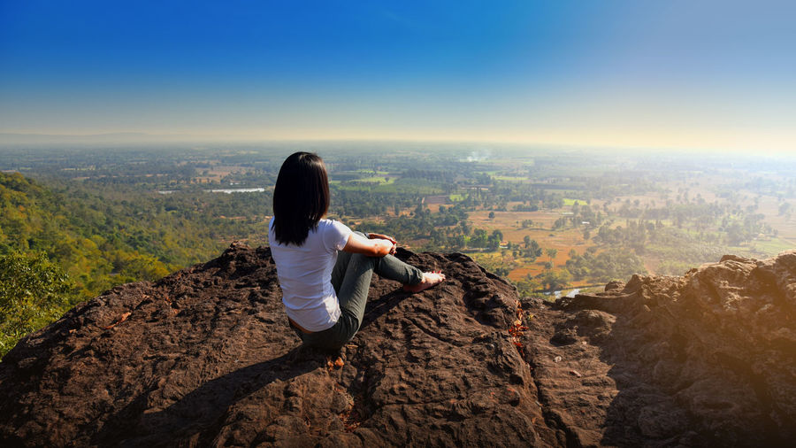 A  woman is sitting on an unusual rock on a mountain overlooking forest