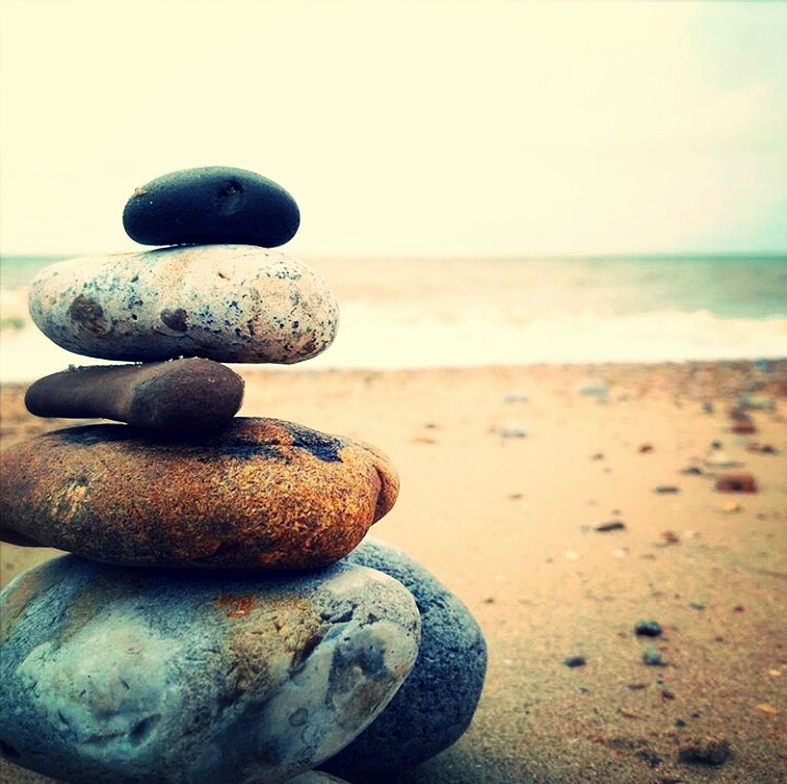 sea, beach, horizon over water, stone - object, shore, water, close-up, focus on foreground, metal, pebble, sky, sand, day, balance, tranquility, nature, rock - object, metallic, no people, outdoors