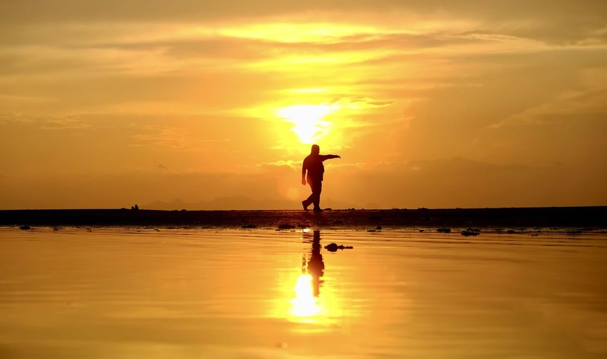 Sky Sunset Silhouette Orange Color Water Scenics - Nature Beauty In Nature Sea Real People Reflection Horizon Over Water Cloud - Sky Standing One Person Lifestyles Horizon Leisure Activity Sun Nature Outdoors Human Arm Arms Raised