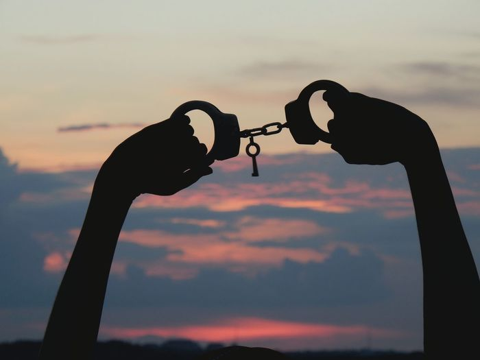 Silhouette Cropped Hands Holding Handcuffs Against Cloudy Sky During Sunset