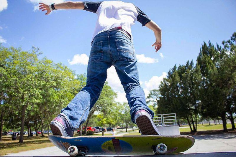 Low section of boy skateboarding in park against sky