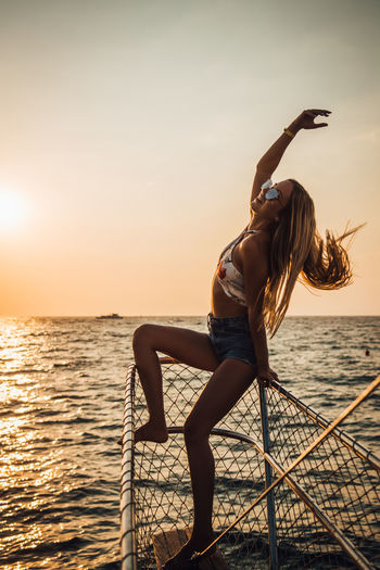 Water Sky Sunset Sea Real People Lifestyles Leisure Activity One Person Beauty In Nature Scenics - Nature Nature Young Adult Women Horizon Over Water Horizon Adult Full Length Young Women Outdoors Hairstyle Arms Raised Human Arm