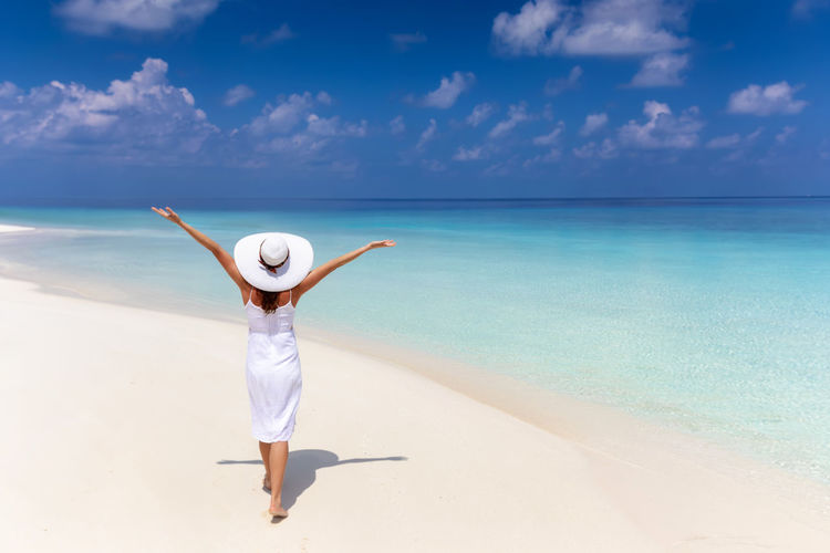 Happy traveler woman in white dress walks on a tropical beach and enjoys her vacation time Sea Sky Horizon Hat Horizon Over Water Water One Person Scenics - Nature Beauty In Nature Trip Clothing Vacations Turquoise Colored Sun Hat Arms Raised Beach Leisure Activity Traveler Tropics Tropical Climate Maldives Freedom Happiness Dress White