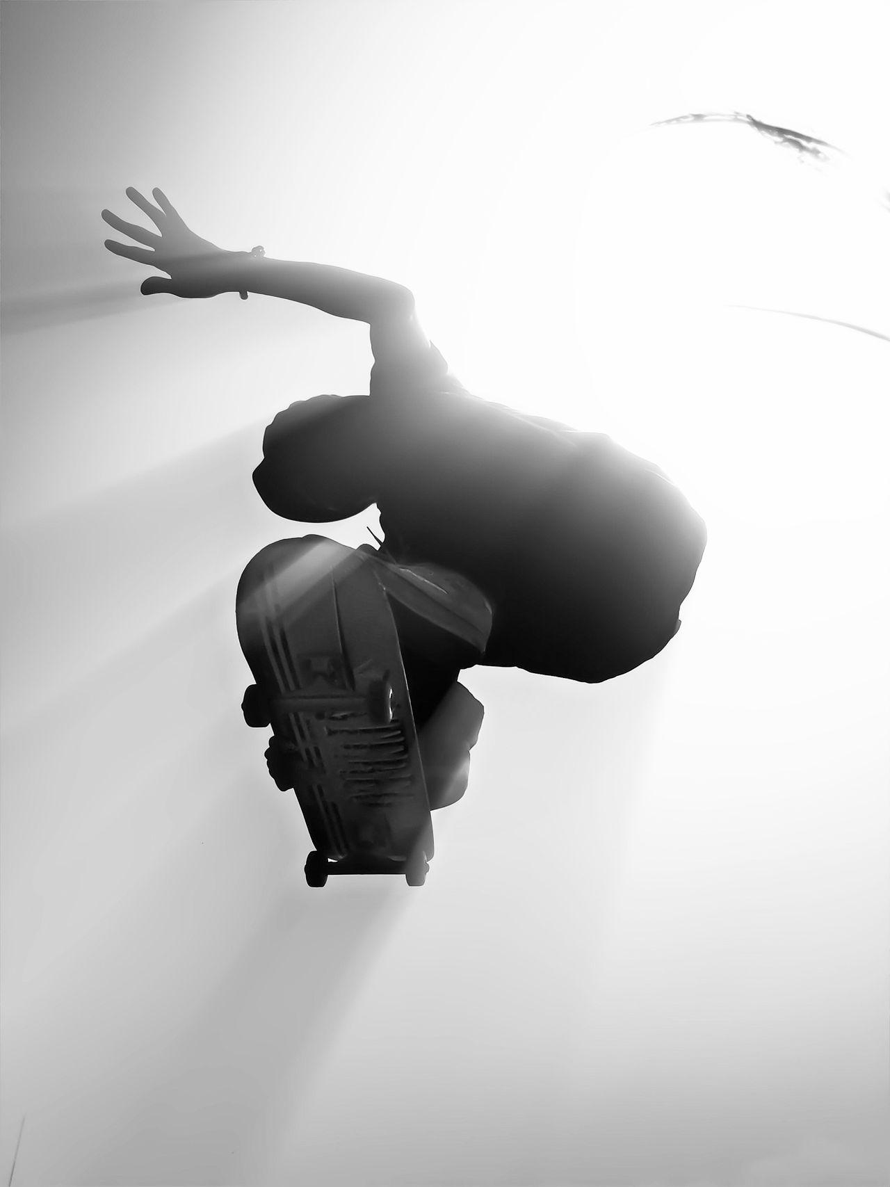 Directly below shot of man skateboarding against clear sky