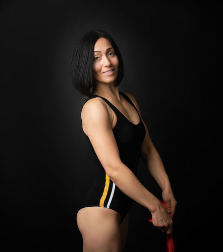 Portrait of athlete standing against black background