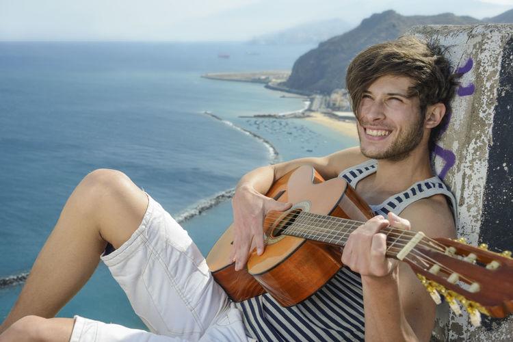 Smiling man playing guitar while sitting on rock