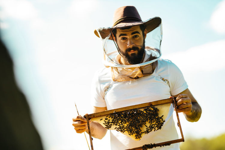Portrait of man with honey bees outdoors