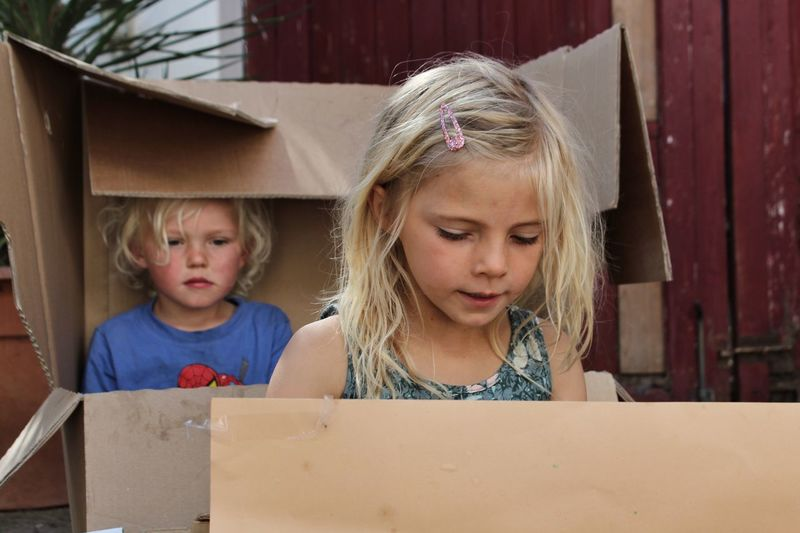 Cute boy and girl looking away while sitting in boxes
