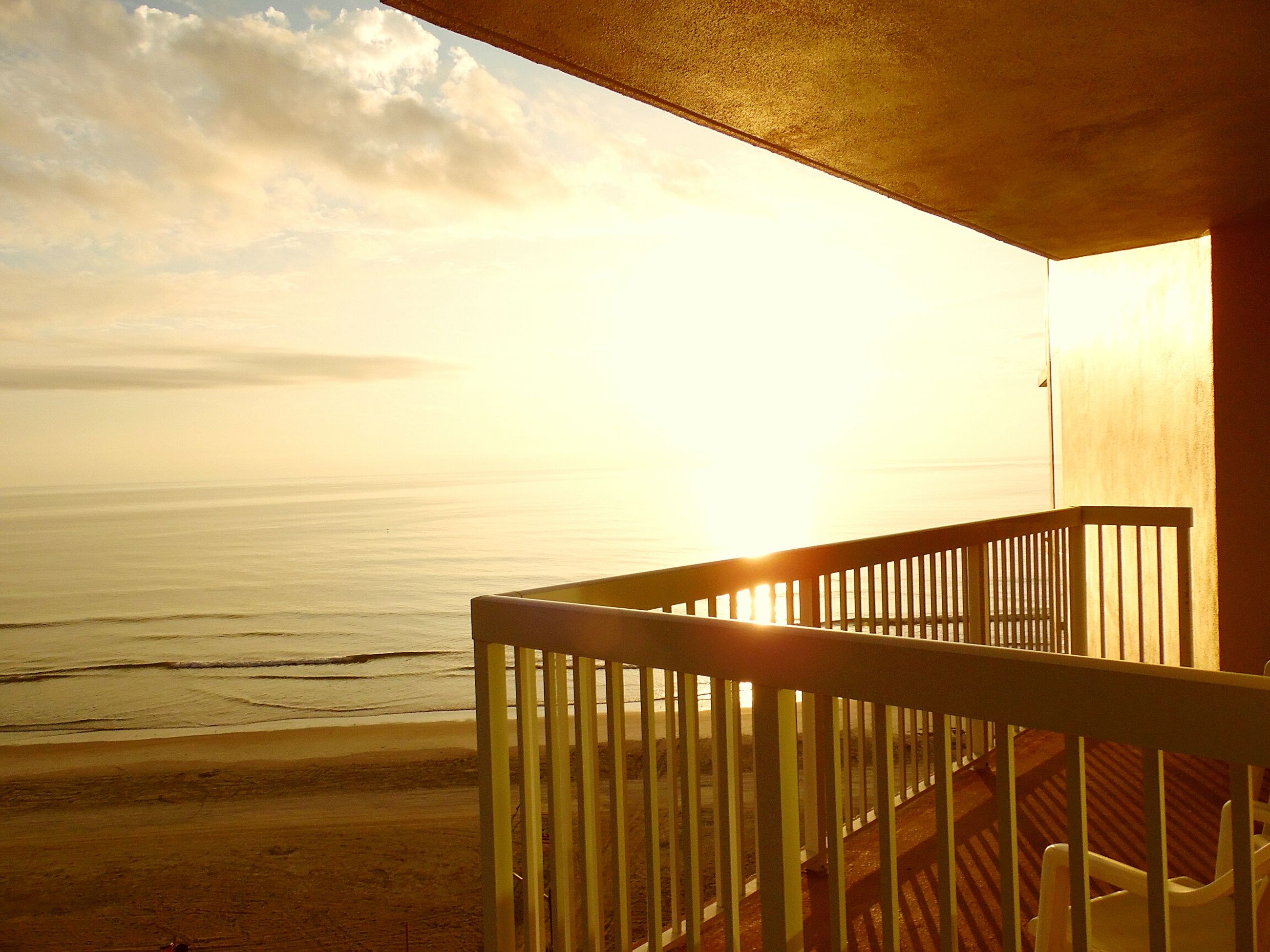 sea, horizon over water, beach, sky, water, sunlight, railing, scenics, tranquil scene, tranquility, sunset, sand, shore, beauty in nature, sun, wood - material, nature, idyllic, pier, built structure