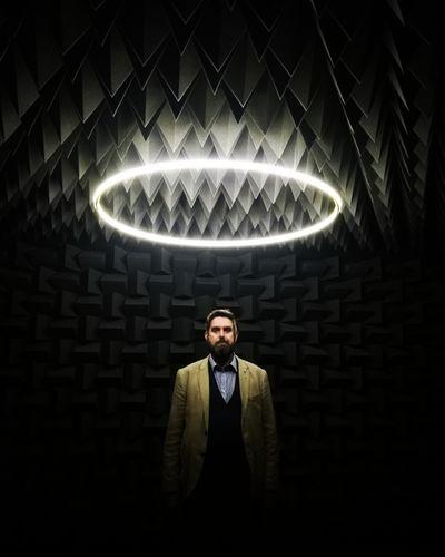 Portrait of man standing in illuminated room