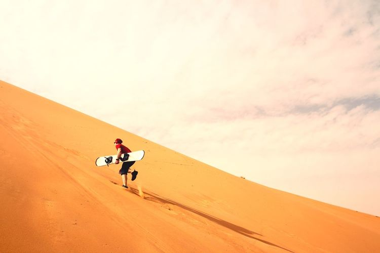 Man with surfboard on sand against sky