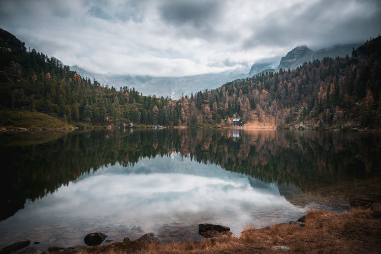 Cabin in the woods at mountain lake reedsee in the austrian alps in gastein in  moody fall colors