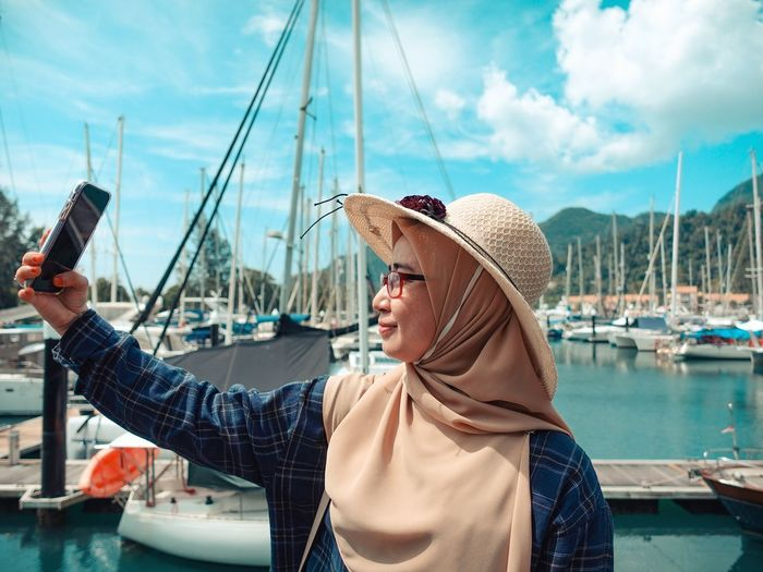 Woman wearing hijab taking selfie at harbor