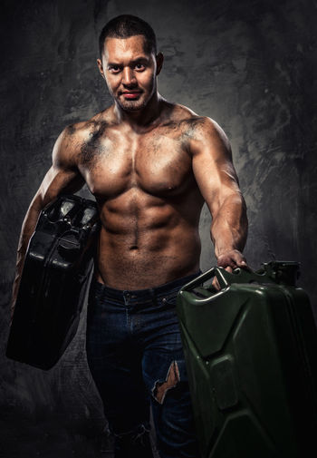 Muscular man with two metal fuel cans indoors Athlete Benzine Container Fuel Gas Gasoline Man Masculinity Adult Canister Energy Flammable Fuel Can Fuel Tank Jerry Jerrycan Men Muscle Muscular Build Oil One Man Only One Person People Petrol Strength