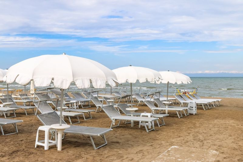 Empty beach with white sunshades against the sky, Italy, Riccione Italy. Riccione Summer Italy Emiliaromagna Rimini Riccione Adriatic Sea Vacation Travel Resort Outdoors No People Chaise-longue Lounge Umbrella Sand Sunshade Sunbed Beach Sky Sea Sand Vacations Tranquil Scene Outdoors Cloud - Sky Horizon Over Water Day Tranquility Water