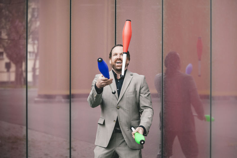 Front View Standing Business One Person Men Business Person Males  Businessman Jugglery Juggling Juggler Business Man Business Dress Fun Circus Colourful Happy Happiness Jean-claude Knobbe Sports Economy Juggling With Money Money Maker Mafioso Playing With Money