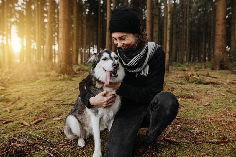 Man with dog sitting in the forest