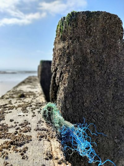 Close-up of rope on rock at beach against sky