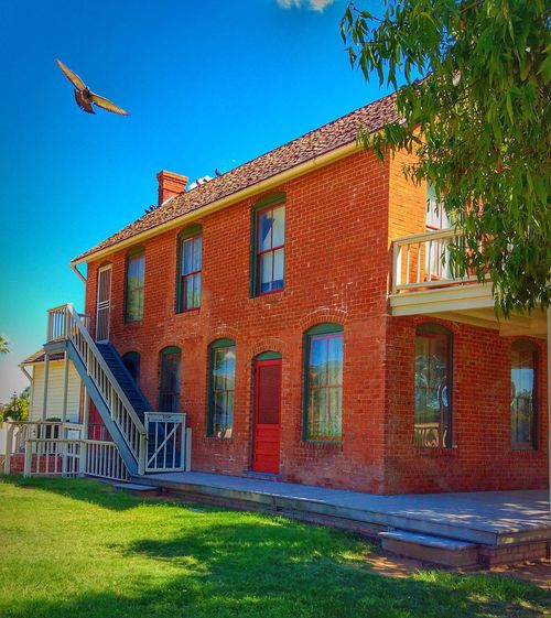Architecture Building Exterior Built Structure Flying Blue Clear Sky Window Grass Mid-air City City Life Outdoors Multi Colored Sky Day No People Red Arizona Historic Ranch Ranch Life Glendale Surface Level Atmospheric Mood Non-urban Scene