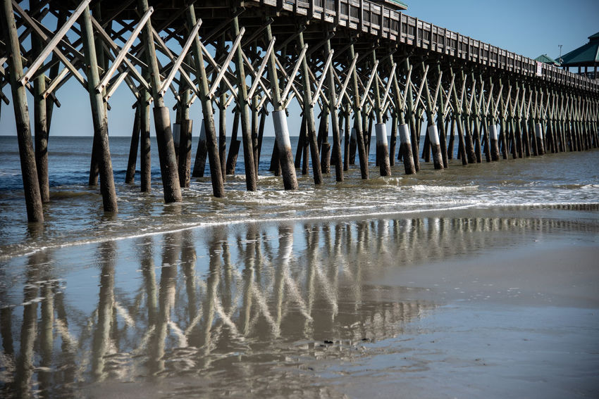 Water Reflection Nature Pier Day Architecture Built Structure No People Sky Waterfront Beach Sea In A Row Outdoors Wooden Post Wood - Material