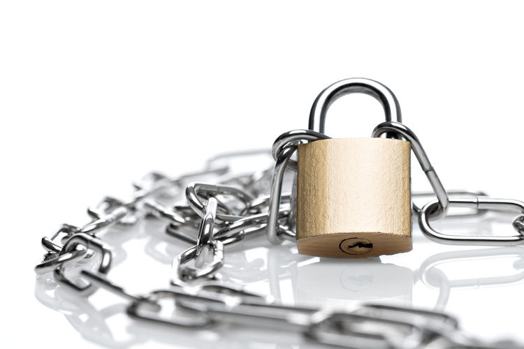 Close-up of padlock and chain on white background