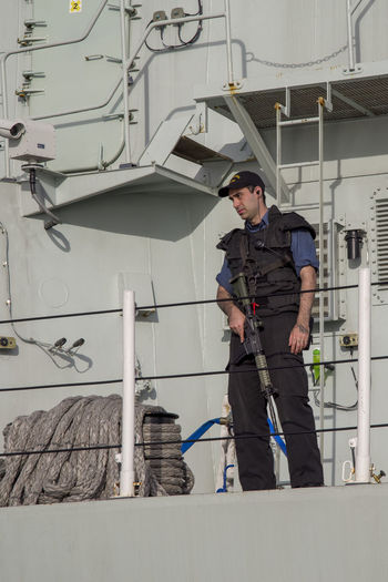 Naval officer with assault rifle HMCS Regina Lonsdale Quay Naval Royal Canadian Navy Wallace Shipyards Assault Boat Dock Navy North Vancouver Rifle Ship Sky