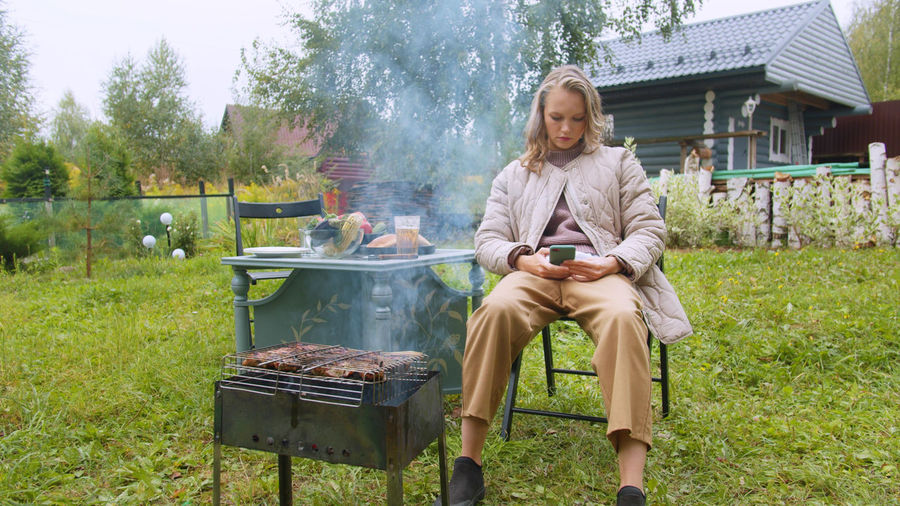 Full length of man sitting on barbecue grill