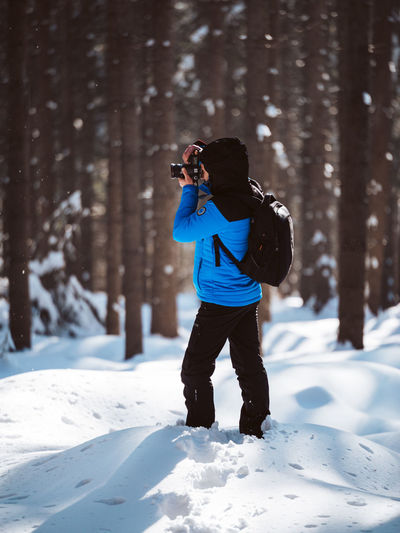 Snow Cold Temperature Winter Photography Themes One Person Technology Camera - Photographic Equipment Leisure Activity Photographing Activity Real People Photographic Equipment Lifestyles Full Length Nature Day Land Tree Digital Camera Warm Clothing Outdoors Photographer Hiking Forest Nature
