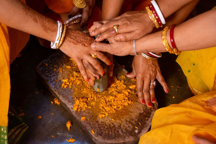 High angle view of women crushing turmeric on stone