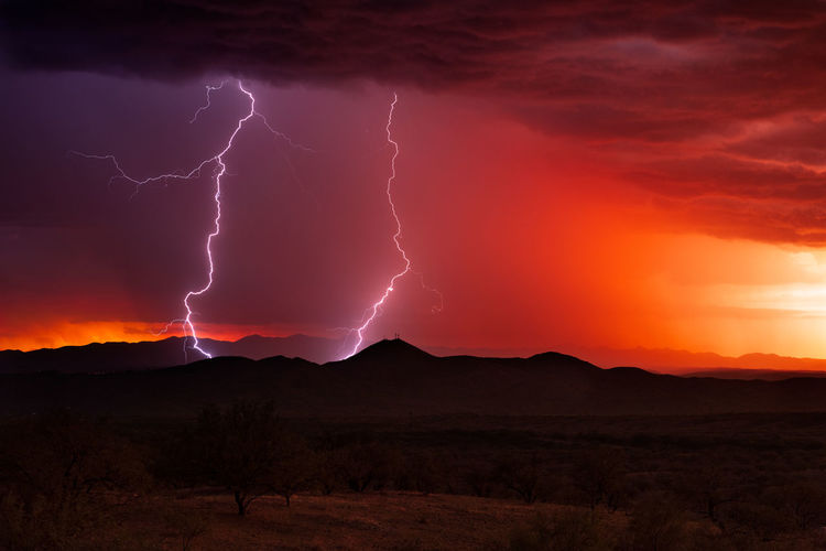 Lightning strikes from a monsoon thunderstorm at sunset over nogales, arizona.