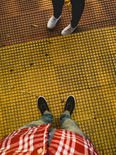 Low section of man and woman standing on tiled floor